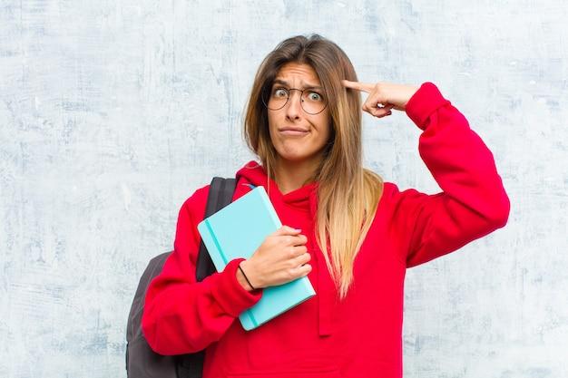 Jovem estudante bonita com um olhar sério e concentrado, fazendo brainstorming e pensando em um problema desafiador