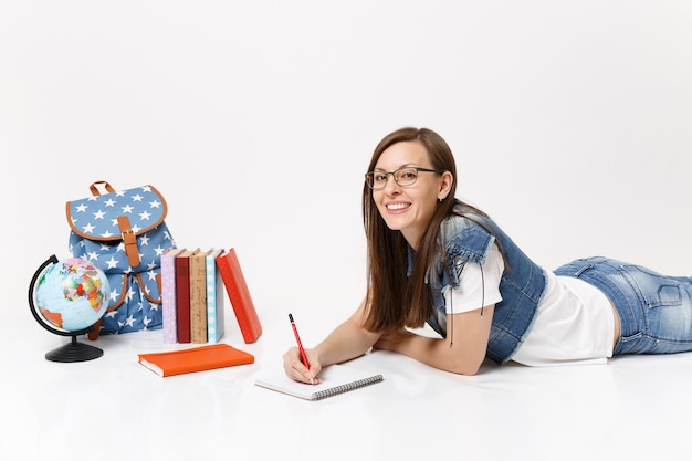 Jovem estudante bonita em óculos de roupas jeans escrevendo notas no caderno e deitada perto do globo, mochila, livro escolar isolado