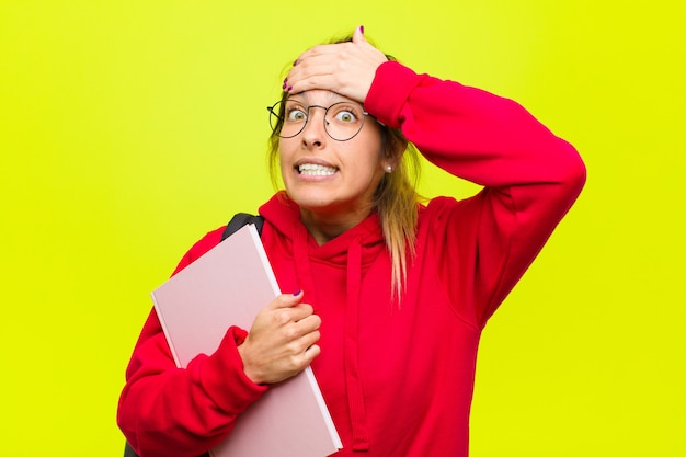 Jovem estudante bonita entrando em pânico por um prazo esquecido, sentindo-se estressada, tendo que encobrir uma bagunça ou erro