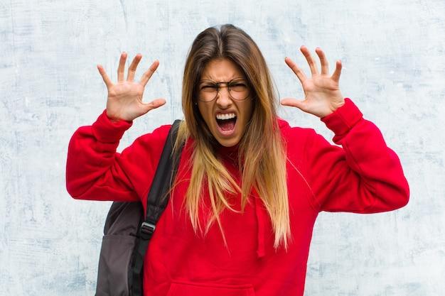 Jovem estudante bonita gritando de pânico ou raiva, chocada, apavorada ou furiosa, com as mãos ao lado da cabeça