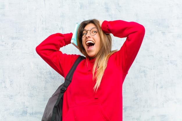 Jovem estudante bonita levantando as mãos à cabeça, boca aberta, sentindo-se extremamente sortudo, surpreso, animado e feliz