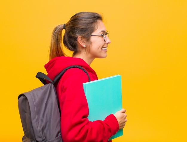 Jovem estudante bonita na vista de perfil, olhando para copiar o espaço à frente, pensando, imaginando ou sonhando acordado