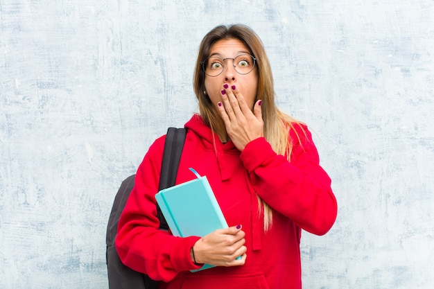 Jovem estudante bonita olhando desagradavelmente chocada, assustada ou preocupada, boca aberta e cobrindo os dois ouvidos com as mãos