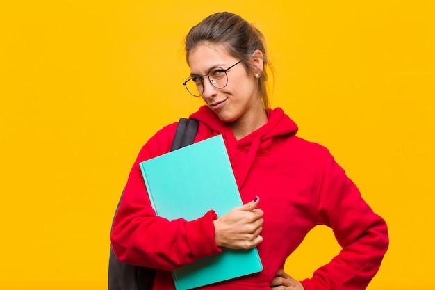 Jovem estudante bonita olhando orgulhosa, confiante, legal, atrevida e arrogante, sorrindo, sentindo-se bem-sucedida