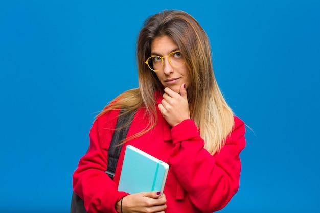 Jovem estudante bonita olhando séria, confusa, incerta e atenciosa, duvidando entre opções ou escolhas