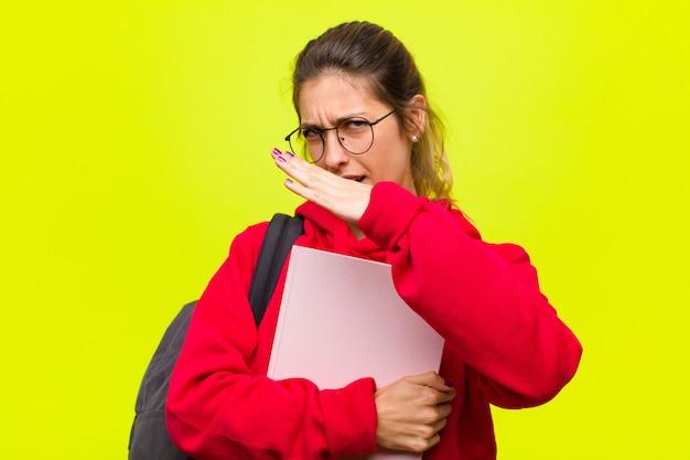 Jovem estudante bonita parecendo irritada e cansada de sua atitude, dizendo o suficiente! mãos cruzadas na frente, dizendo para parar