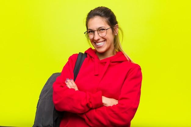 Jovem estudante bonita parecendo um empreendedor feliz, orgulhoso e satisfeito, sorrindo com os braços cruzados