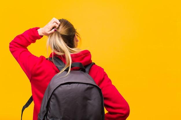 Jovem estudante bonita pensando ou duvidando, coçando a cabeça, sentindo-se confuso e confuso, vista traseira ou traseira