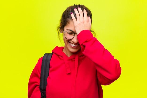 Jovem estudante bonita rindo e dando um tapa na testa como se dissesse 'oh! eu esqueci ou isso foi um erro estúpido