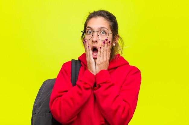 Jovem estudante bonita se sentindo chocada e assustada, parecendo aterrorizada com a boca aberta e as mãos nas bochechas