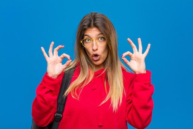 Jovem estudante bonita se sentindo chocado espantado e surpreso mostrando aprovação fazendo sinal de ok com as duas mãos