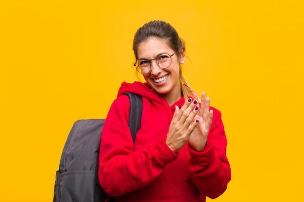 Jovem estudante bonita se sentindo feliz e bem-sucedida, sorrindo e batendo palmas de mãos, dizendo parabéns com um aplauso
