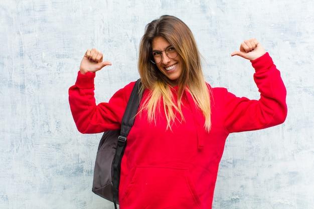 Jovem estudante bonita se sentindo orgulhosa, arrogante e confiante, parecendo satisfeita e bem-sucedida, apontando para si mesma