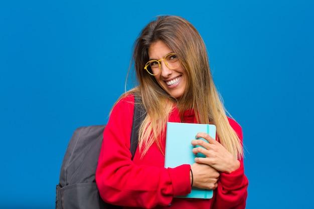 Jovem estudante bonita se sentindo romântico, feliz e apaixonado, sorrindo alegremente e segurando as mãos perto do coração