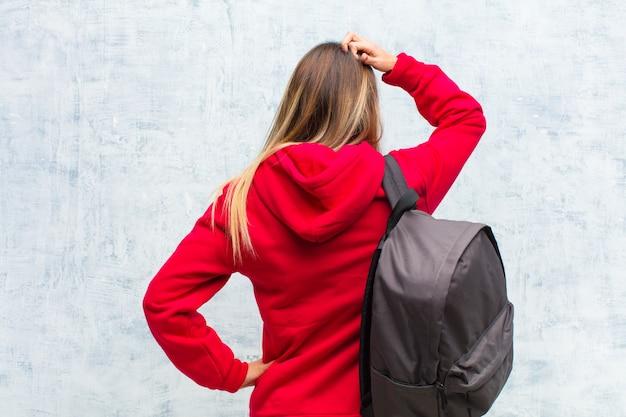 Jovem estudante bonita se sentindo sem noção e confusa, pensando em uma solução, com a mão na anca e outra na cabeça