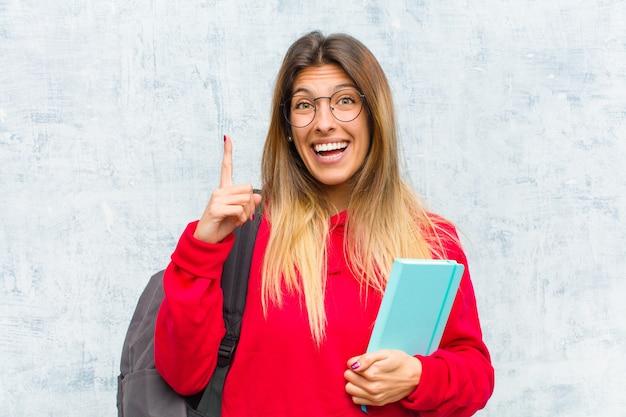 Jovem estudante bonita se sentindo um gênio feliz e animado depois de perceber uma ideia, levantando alegremente o dedo, eureka!