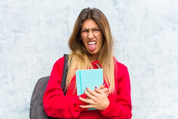 Jovem estudante bonita sentindo nojo e irritada, enfiando a língua para fora, não gostando de algo desagradável e nojento