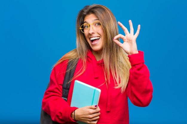 Jovem estudante bonita, sentindo-se bem-sucedida e satisfeita, sorrindo com a boca aberta, fazendo sinal de bem com a mão