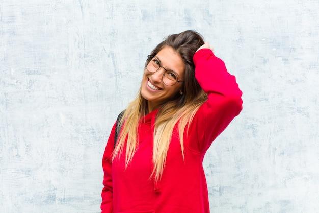 Jovem estudante bonita sorrindo alegre e casualmente, levando a mão à cabeça com um olhar positivo, feliz e confiante