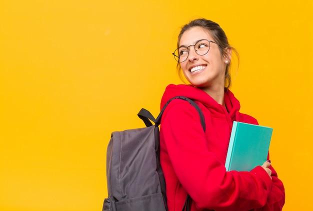 Jovem estudante bonita sorrindo alegremente, sentindo-se feliz, satisfeito e relaxado, com os braços cruzados e olhando para o lado