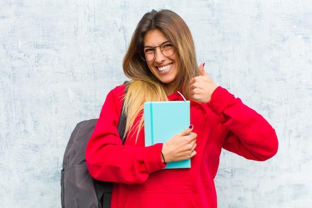 Jovem estudante bonita sorrindo amplamente olhando feliz, positivo, confiante e bem sucedido, com os dois polegares para cima
