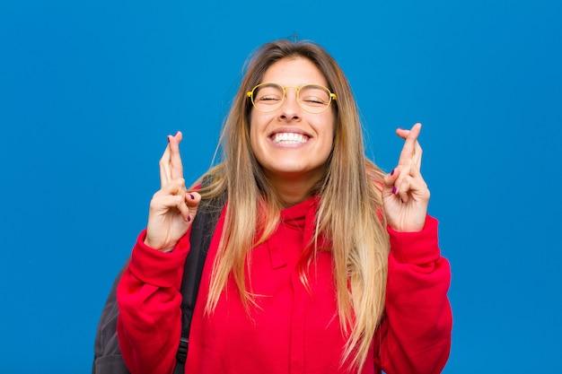 Jovem estudante bonita sorrindo e cruzando ansiosamente os dois dedos, sentindo-se preocupada e desejando ou esperando boa sorte