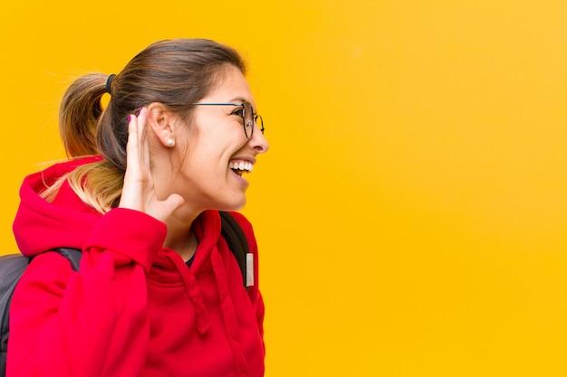 Jovem estudante bonita sorrindo, olhando curiosamente para o lado, tentando ouvir fofocas ou ouvir um segredo