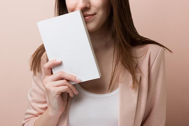 Jovem estudante bonita sorrisos e mantém o livro vazio, isolado no fundo rosa