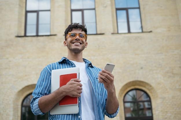 Jovem estudante bonito segurando laptop, livro, telefone celular, caminhando para a universidade