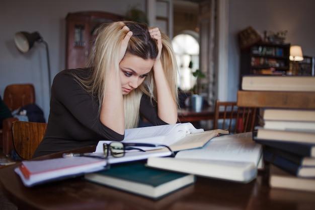 Jovem estudante cansada da universidade. preparando lições para o exame e aprendendo na biblioteca pública.