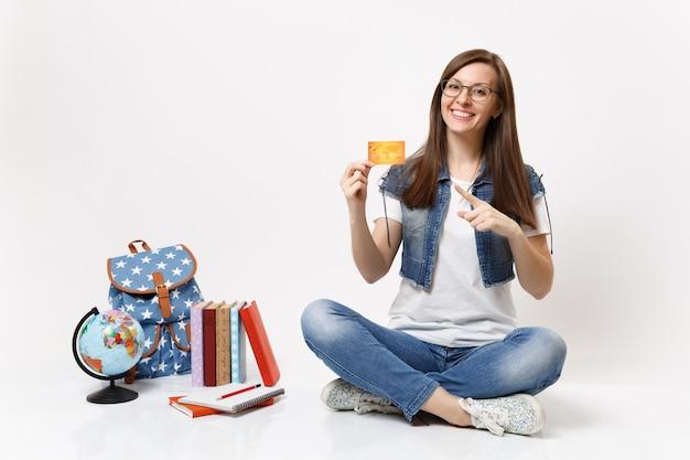 Jovem estudante casual alegre de óculos apontando o dedo indicador no cartão de crédito, sentada perto da mochila globo, livros escolares isolados