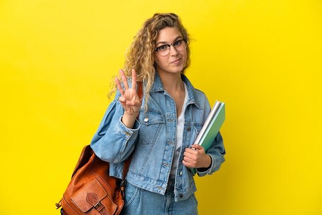 Jovem estudante caucasiana isolada em um fundo amarelo feliz e contando três com os dedos