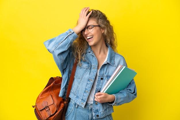 Jovem estudante caucasiana isolada em um fundo amarelo percebeu algo e pretendendo a solução