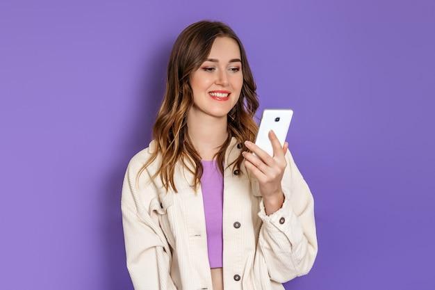 Jovem estudante caucasiana vestindo jaqueta de veludo cotelê bege, olhando para a tela do telefone e sorrindo isolada em fundo lilás. copie o espaço