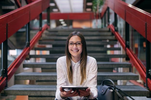 Jovem estudante caucasiano com cabelos castanhos e óculos usando o tablet enquanto está sentado nas escadas no prédio da faculdade.