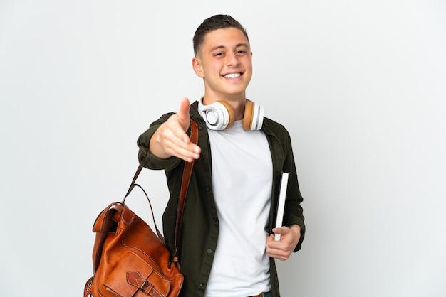 Jovem estudante caucasiano isolado na parede branca apertando as mãos para fechar um bom negócio