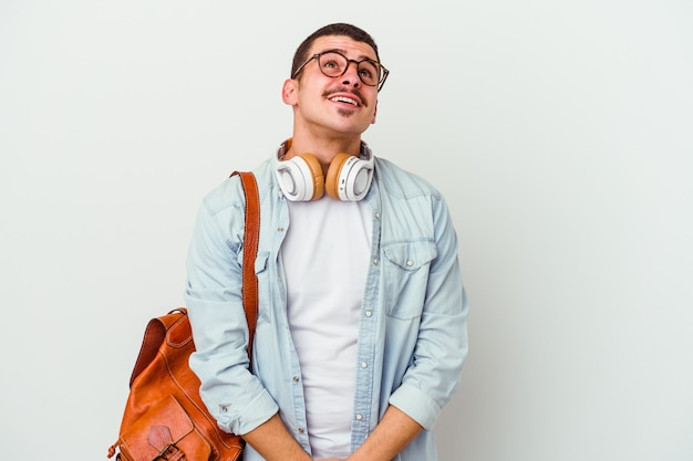 Jovem estudante caucasiano ouvindo música isolada na parede branca e sonhando em alcançar objetivos e propósitos