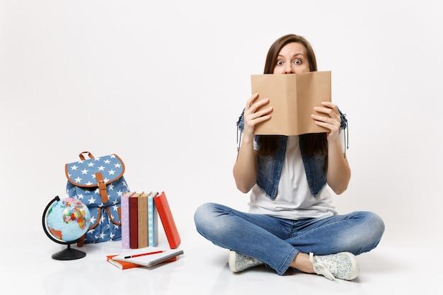 Jovem estudante chocada com roupas jeans, cobrindo o rosto com um livro lido, sentada perto do globo, mochila, livros escolares isolados