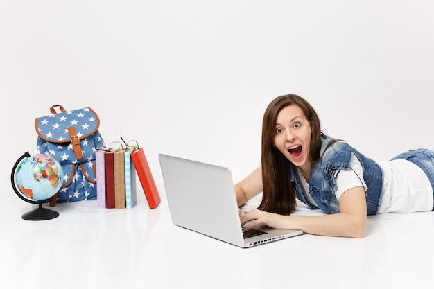 Jovem estudante chocada com roupas jeans, trabalhando em um computador laptop, deitada perto do globo, mochila, livros escolares isolados