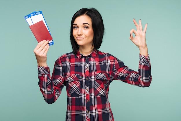 Jovem estudante chocada e animada segurando o bilhete do cartão de embarque do passaporte e mostrando cantar ok isolado no fundo azul-petróleo.