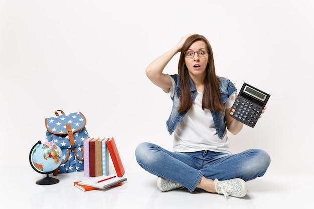 Jovem estudante chocada e assustada segurando uma calculadora agarrada à cabeça, aprendendo matemática, sentada perto do globo, mochila, livros escolares isolados