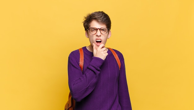 Jovem estudante com a boca e os olhos bem abertos e a mão no queixo sentindo-se desagradavelmente chocado dizendo o quê ou uau