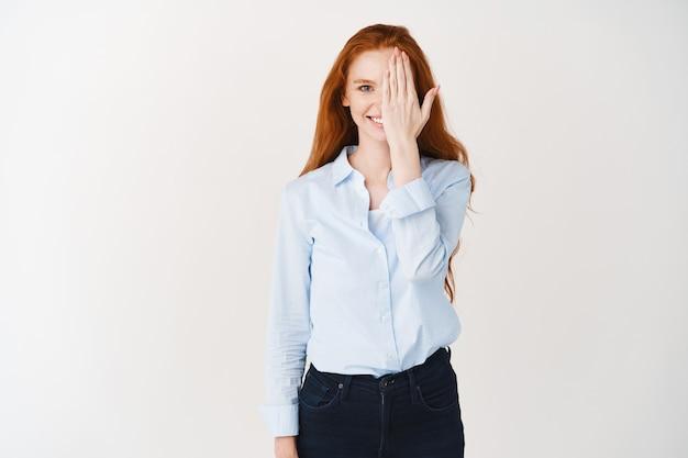 Jovem estudante com cabelos ruivos e pele clara, sorrindo e cobrindo metade do rosto com a mão, verificando a visão, em pé sobre uma parede branca