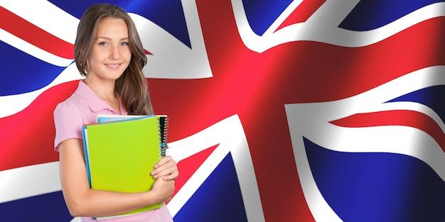 Jovem estudante com livros sobre o fundo da bandeira britânica