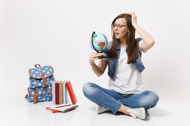 Jovem estudante curiosa e inteligente coçando a cabeça segurando um globo do mundo, aprendendo sobre os países, sentada perto da mochila de livros escolares isolados