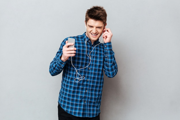 Jovem estudante curtindo música em fones de ouvido no smartphone