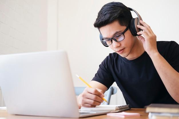 Jovem estudante de colagem usando computador e dispositivo móvel, estudando online. educação e aprendizagem online.