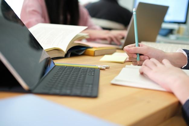 Jovem estudante de colagem usando computador e tablet digital, estudando online.