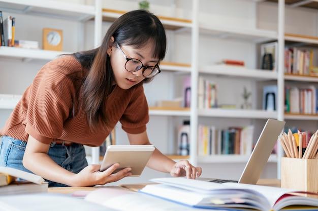 Jovem estudante de colagem usando o computador e o dispositivo móvel, estudando on-line.