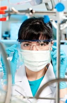 Jovem estudante de medicina na máscara, óculos de proteção olha para a câmera no laboratório de testes de pesquisa